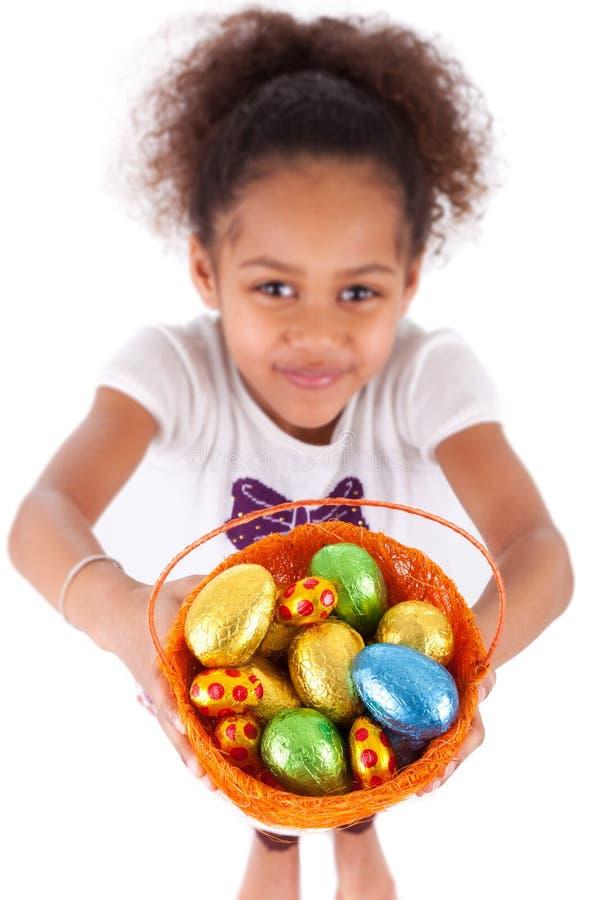 Menina asiática africana que guardara o ovo do éster do chocolate foto de stock