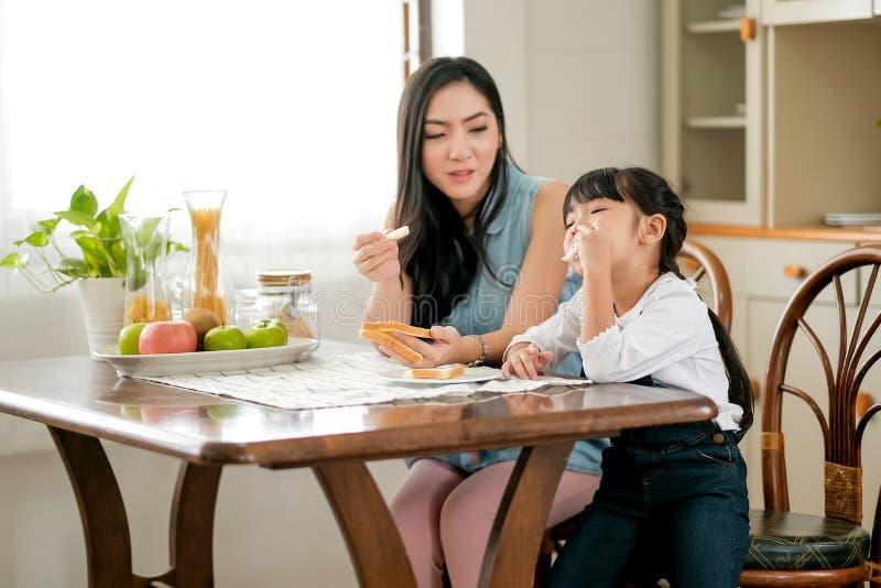 A menina asiática aprecia com pão que come e senta-se perto de sua mãe na cozinha com fruto na tabela O foco principal é pequeno imagens de stock royalty free