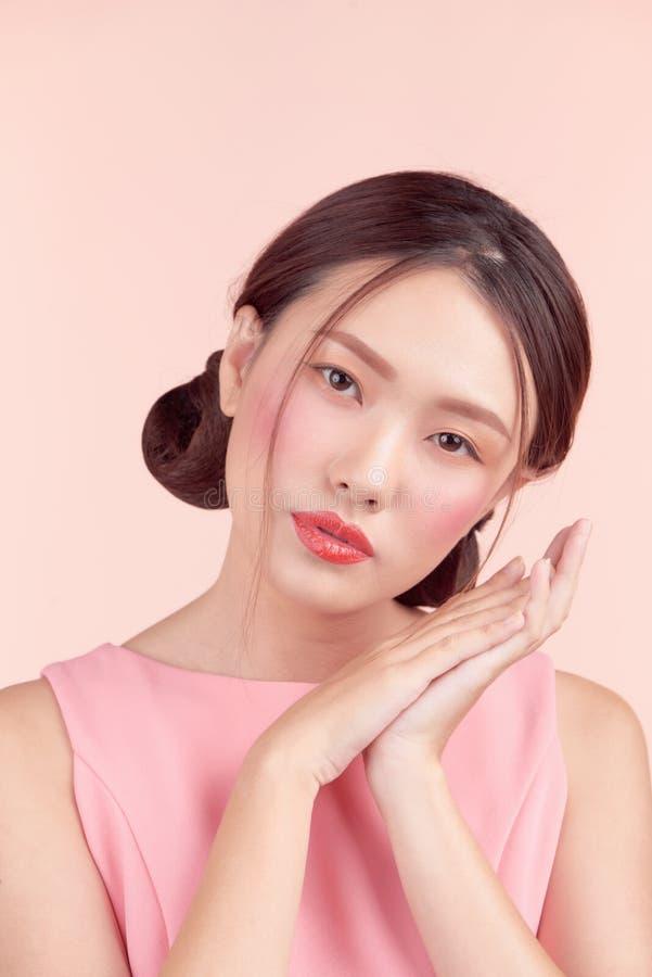 Menina asiática bonita com composição profissional e o penteado à moda isolados no rosa Cosméticos e composição fotos de stock royalty free