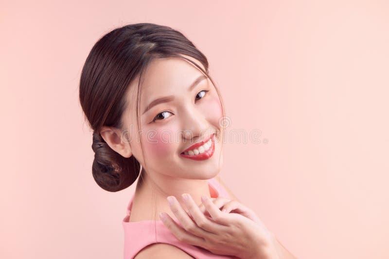 Menina asiática bonita com composição profissional e o penteado à moda isolados no rosa Cosméticos e composição foto de stock royalty free