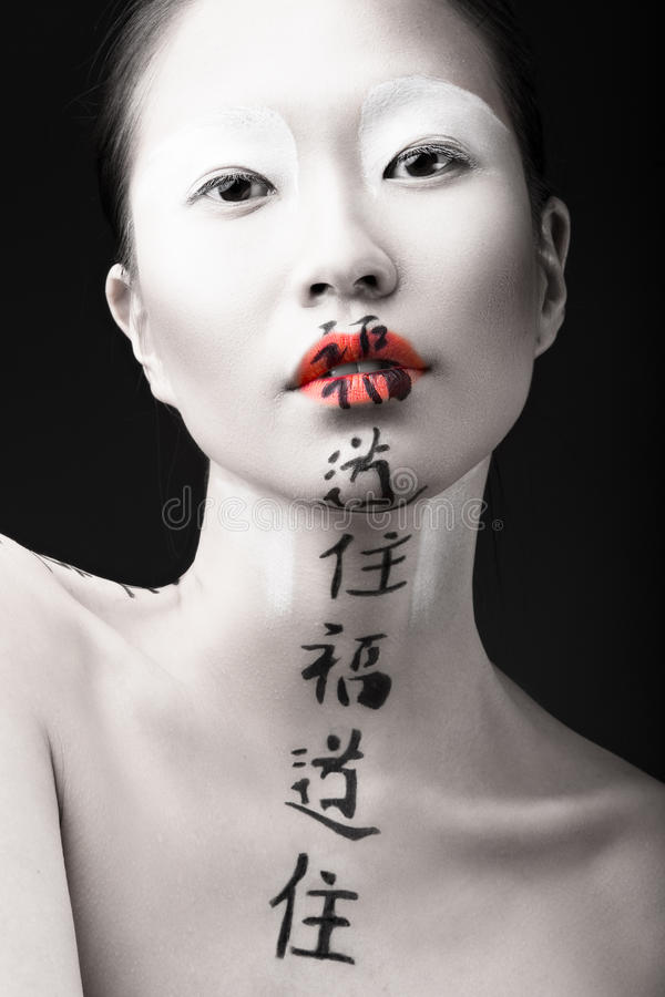 Menina asiática bonita com pele branca, os bordos vermelhos e foto de stock