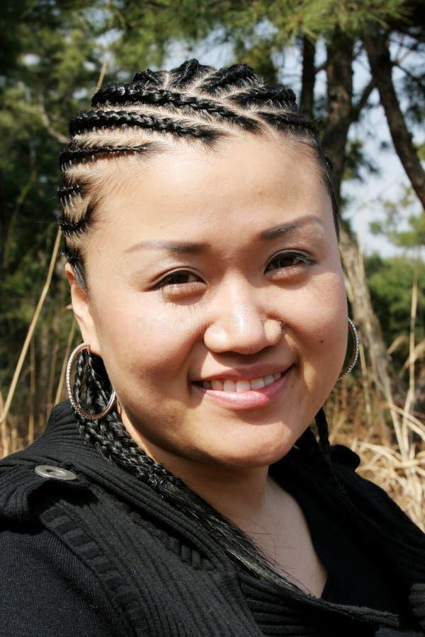 Menina asiática bonita com tranças fotografia de stock