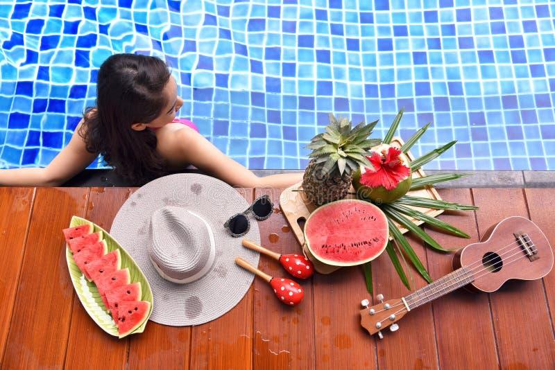 Menina asiática bonita do biquini que relaxa na piscina fotografia de stock