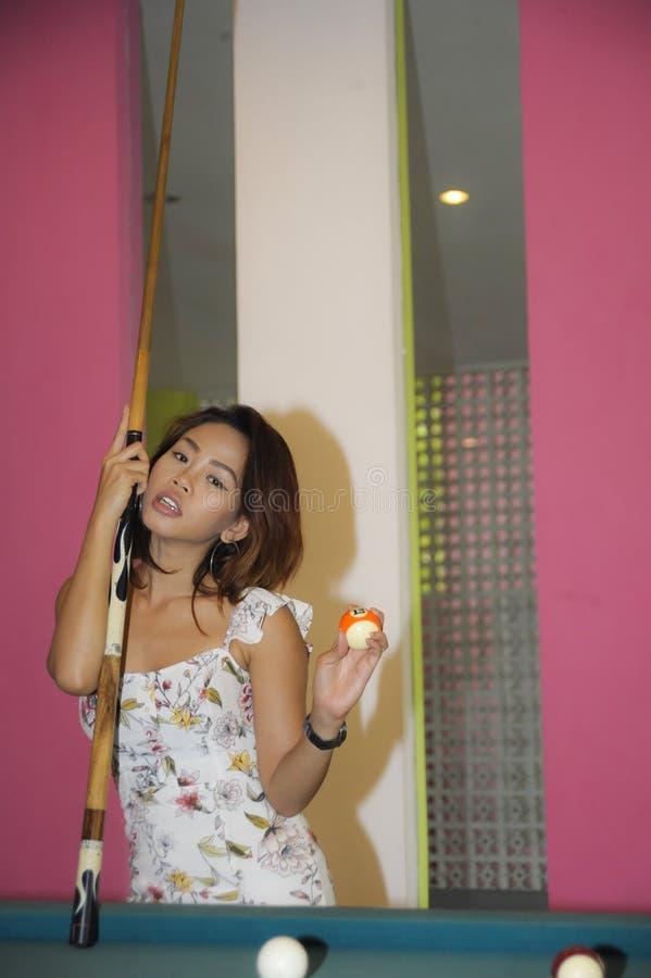 Menina asiática bonita e 'sexy' nova que joga a sinuca que levanta com bola e vara na mesa de bilhar no clube noturno ou na barra imagens de stock royalty free