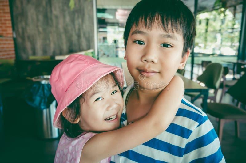 A menina asiática bonita enrolou seu braço do ` s o ombro do ` s do irmão Vint fotografia de stock royalty free