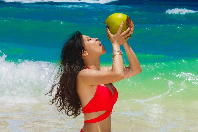 Menina asiática bonita nova com cabelo preto longo no biquini vermelho, fotos de stock