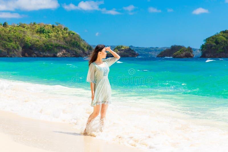 Menina asiática bonita nova no vestido azul na praia de um trop imagens de stock royalty free