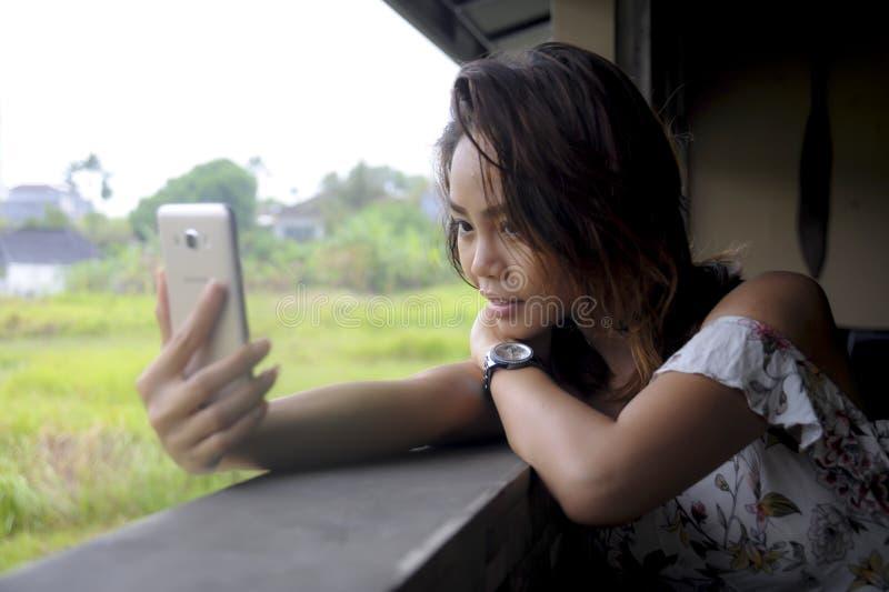 Menina asiática bonita nova que toma a imagem do selfie com assento feliz de sorriso da câmera do telefone celular fora na cafeta fotos de stock