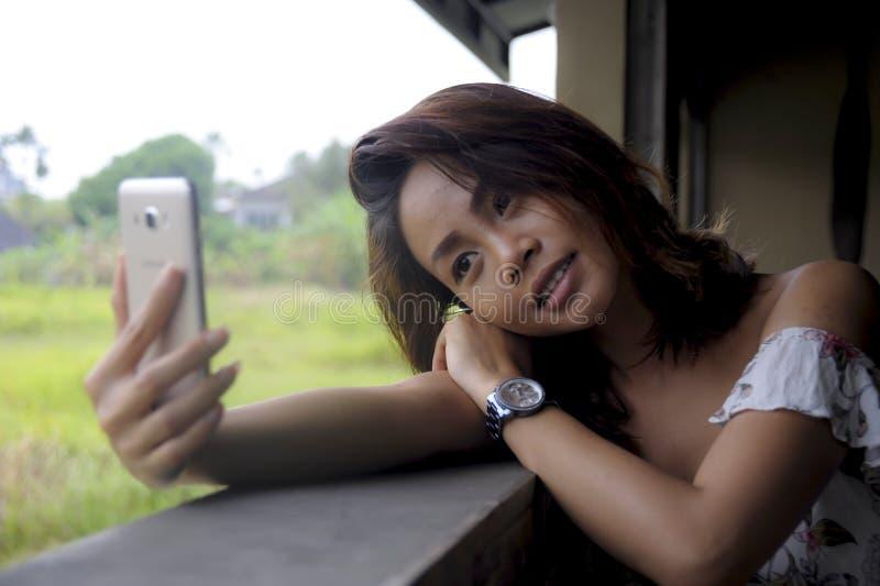 Menina asiática bonita nova que toma a imagem do selfie com assento feliz de sorriso da câmera do telefone celular fora na cafeta imagem de stock