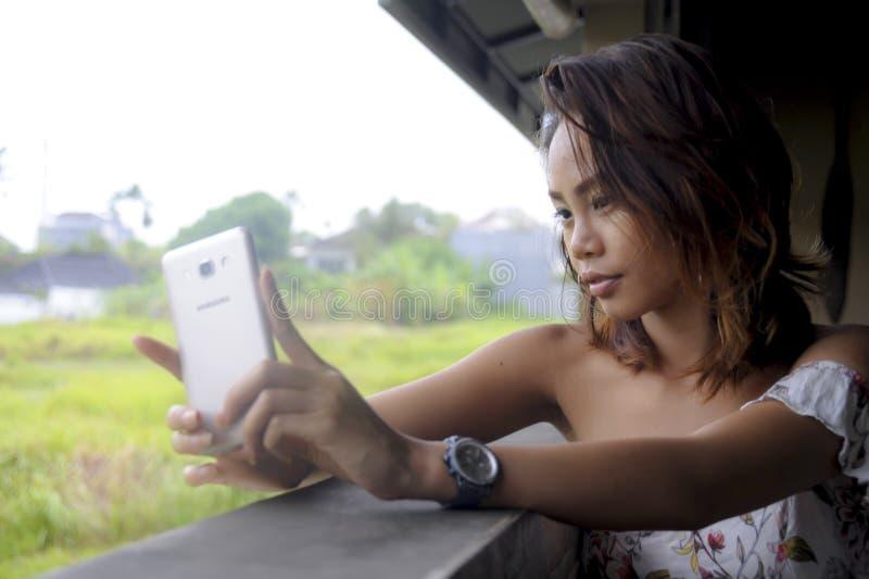 Menina asiática bonita nova que toma a imagem do selfie com assento feliz de sorriso da câmera do telefone celular fora na cafeta fotografia de stock