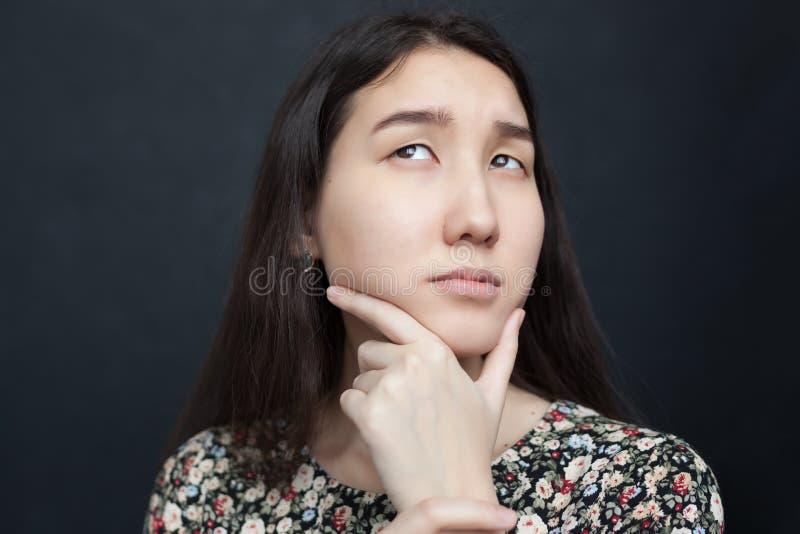 A menina asiática bonita olha acima pensativamente, duvidando o decisio imagem de stock
