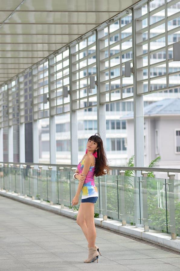 Menina asiática bonita que mostra o vigor jovem na ponte pedestre fotografia de stock royalty free
