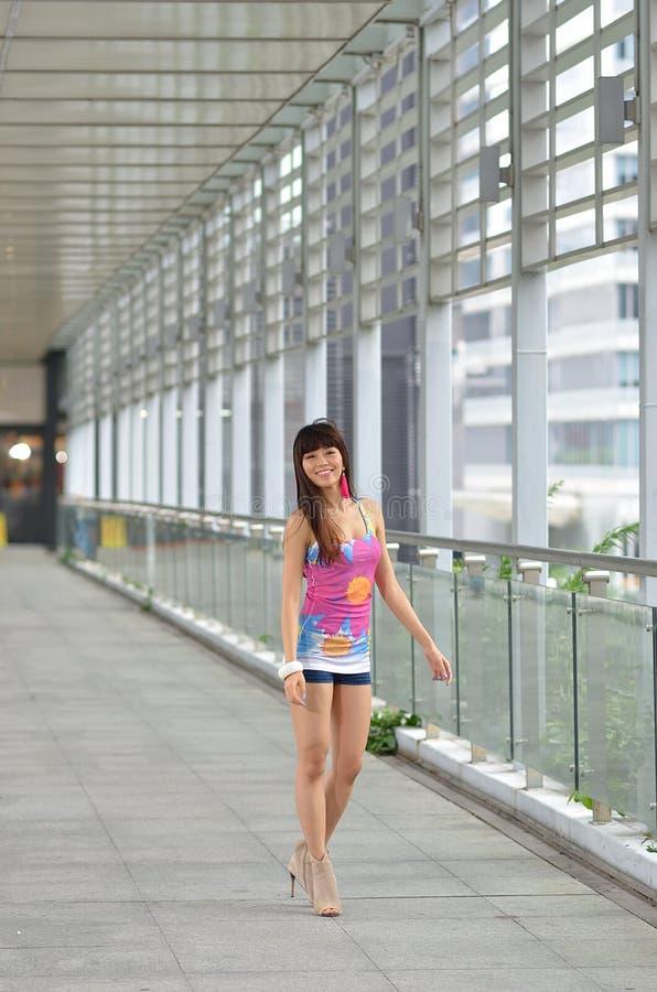 Menina asiática bonita que mostra o vigor jovem na ponte pedestre fotos de stock royalty free