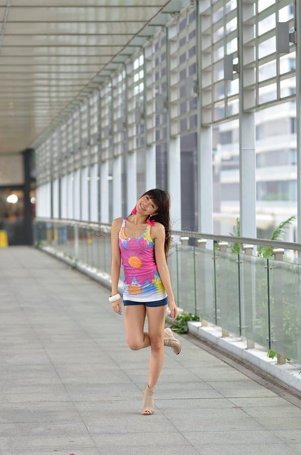 Menina asiática bonita que mostra o vigor jovem na ponte pedestre imagens de stock royalty free