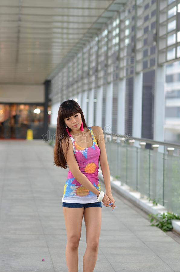 Menina asiática bonita que mostra o vigor jovem na ponte pedestre foto de stock
