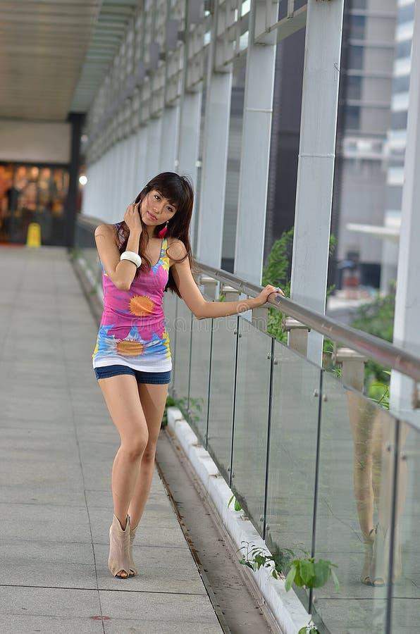 Menina asiática bonita que mostra o vigor jovem na ponte pedestre imagem de stock royalty free