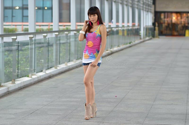 Menina asiática bonita que mostra o vigor jovem na ponte pedestre imagens de stock