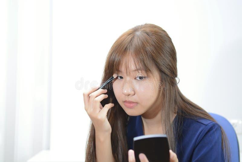 A menina asiática bonita que tem compõe a aplicação sobre os wi dos olhos fotografia de stock royalty free
