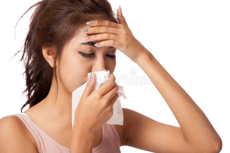 A menina asiática bonita tem a gripe e a febre foto de stock