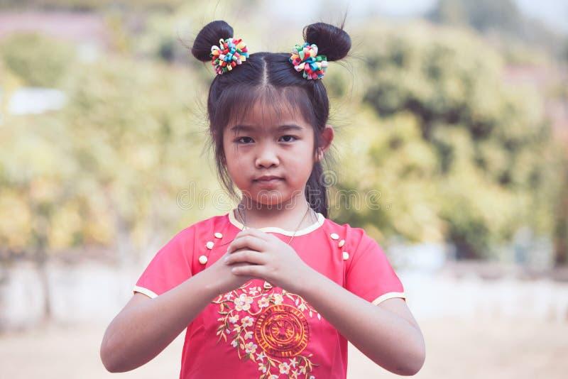 Menina asiática bonito da criança com gesto das felicitações imagens de stock royalty free