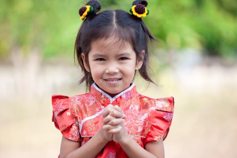 Menina asiática bonito da criança com gesto das felicitações imagem de stock