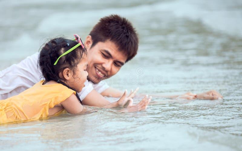 Menina asiática bonito da criança e seu pai que jogam na praia foto de stock royalty free