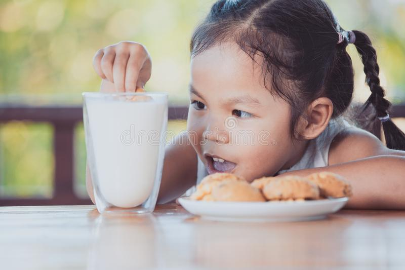 Menina asiática bonito da criança pequena que come a cookie com leite imagens de stock