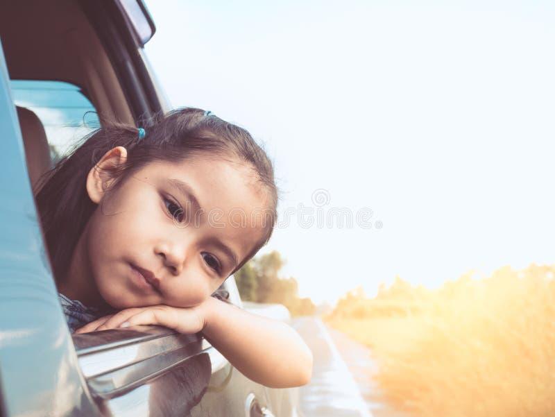 Menina asiática bonito da criança pequena que viaja pelo carro foto de stock