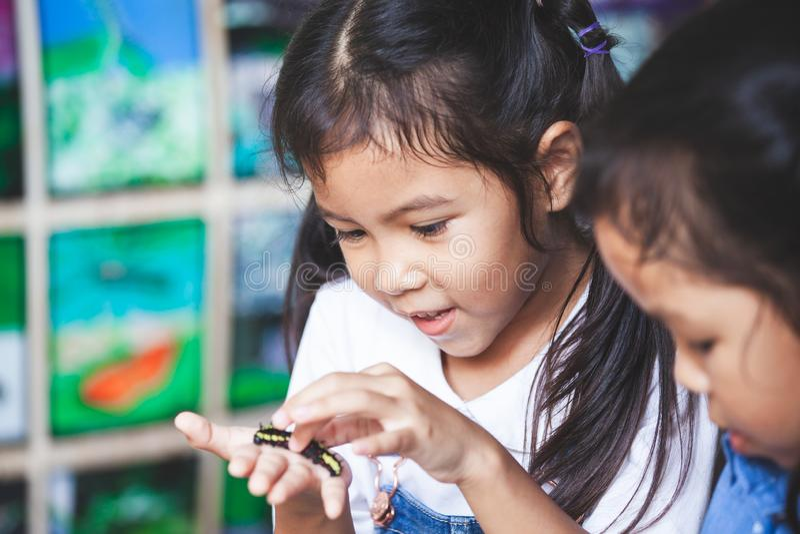 Menina asiática bonito da criança que guarda e que joga com lagarta preta imagem de stock royalty free