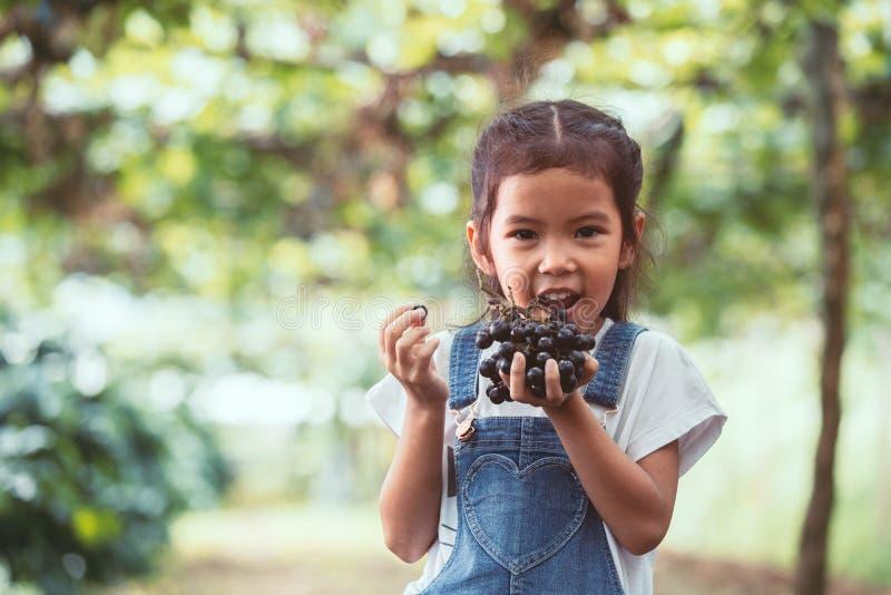 Menina asiática bonito da criança que guarda o grupo de uvas vermelhas imagens de stock royalty free