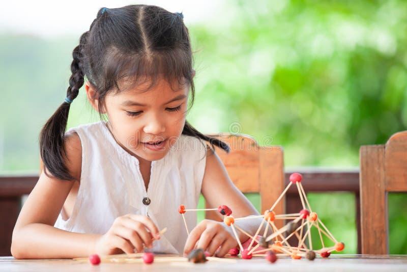 Menina asiática bonito da criança que joga e que cria com a massa do jogo fotografia de stock royalty free