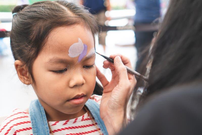 A menina asiática bonito da criança que obtém a cara pintou fotografia de stock