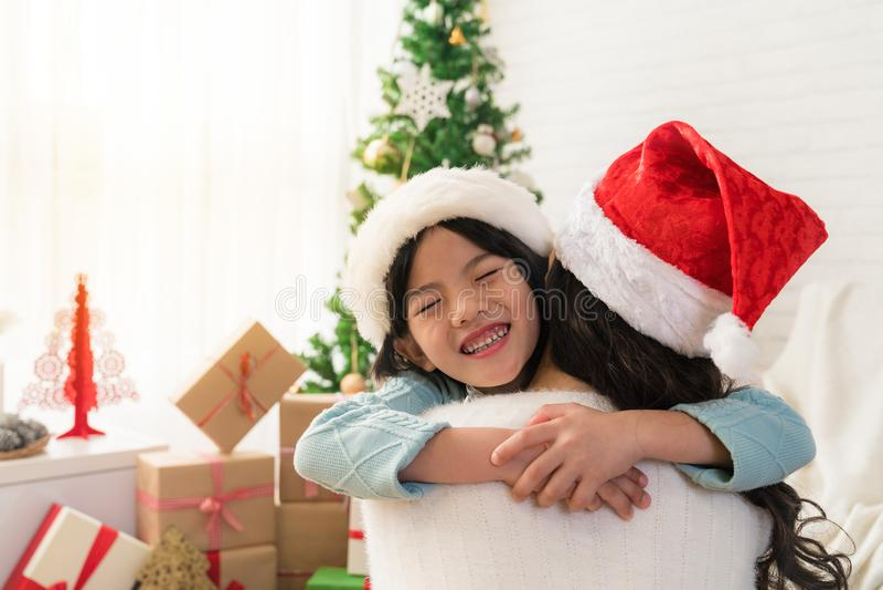 A menina asiática bonito da filha dá-a um abraço da mãe imagens de stock