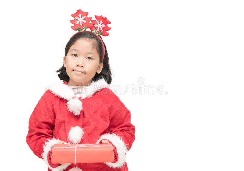Menina asiática bonito no terno de Papai Noel que guarda a caixa de presente fotografia de stock