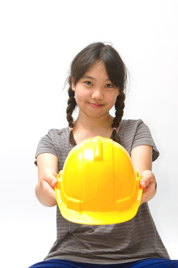 Menina asiática bonito que dá um capacete da construção foto de stock