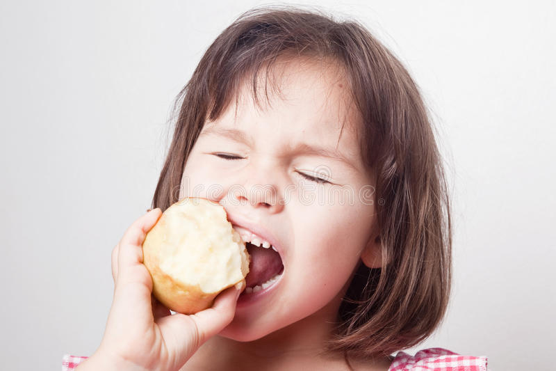 Menina asiática bonito que morde uma maçã foto de stock royalty free