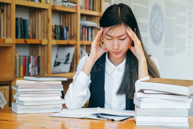 Menina asiática bonito que senta-se em uma biblioteca, cercada pelos livros, pensando sobre o estudo Dor de cabeça, enxaqueca, es foto de stock
