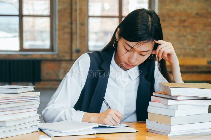 Menina asiática bonito que senta-se em uma biblioteca, cercada pelos livros, pensando sobre o estudo O estudante adolescente prep imagens de stock royalty free