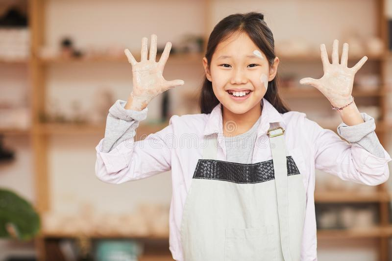 Menina asiática brincalhão na classe da cerâmica fotografia de stock