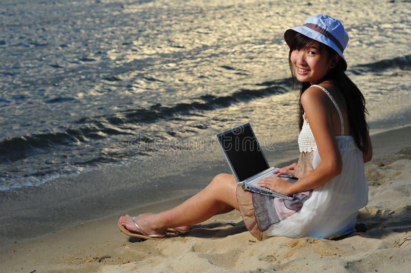 Menina asiática chinesa pequena na praia com portátil fotografia de stock royalty free