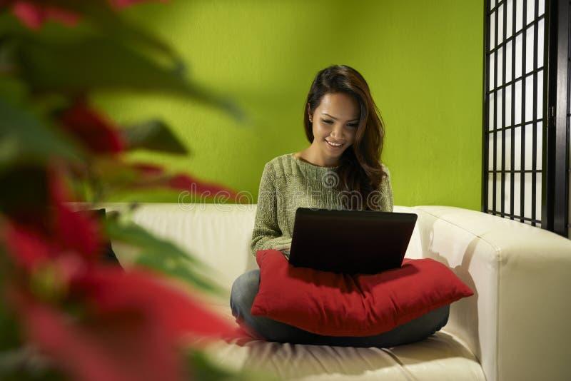 Menina asiática com o computador que senta-se no sofá em casa foto de stock royalty free