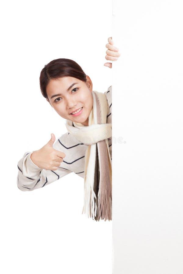 Menina asiática com o lenço que espreita dos polegares vazios de trás do sinal acima imagem de stock