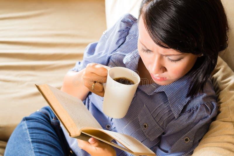 Menina asiática com o livro de leitura do copo foto de stock royalty free