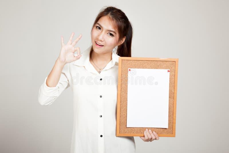 Menina asiática com o pino do papel vazio na placa da cortiça fotos de stock