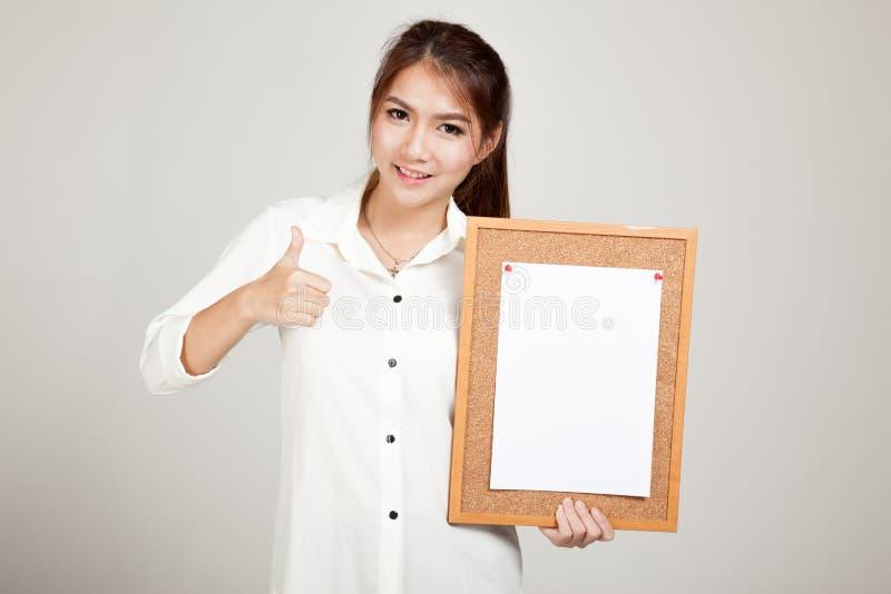 Menina asiática com o pino do papel vazio na placa da cortiça imagem de stock