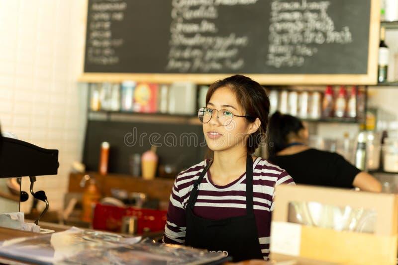 Menina asiática com posição vestindo do avental da empregada de mesa dos vidros na cafetaria imagens de stock
