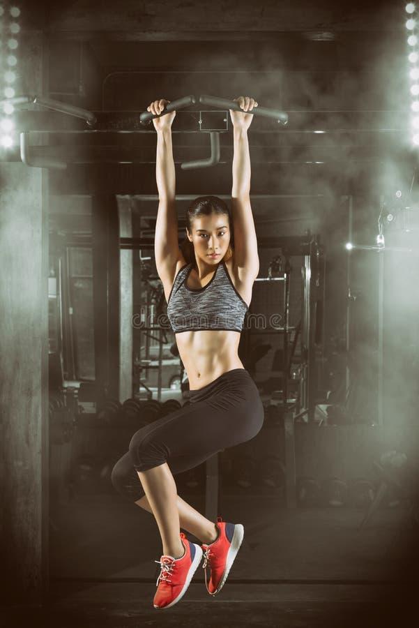 A menina asiática da aptidão com o corpo perfeito da forma que faz elevações levanta no gym foto de stock royalty free