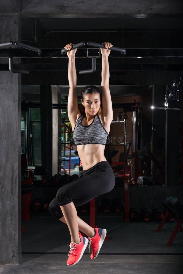 A menina asiática da aptidão com o corpo perfeito da forma que faz elevações levanta no gym fotos de stock royalty free