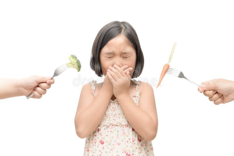 Menina asiática da criança com expressão da aversão contra vegetais mim foto de stock royalty free