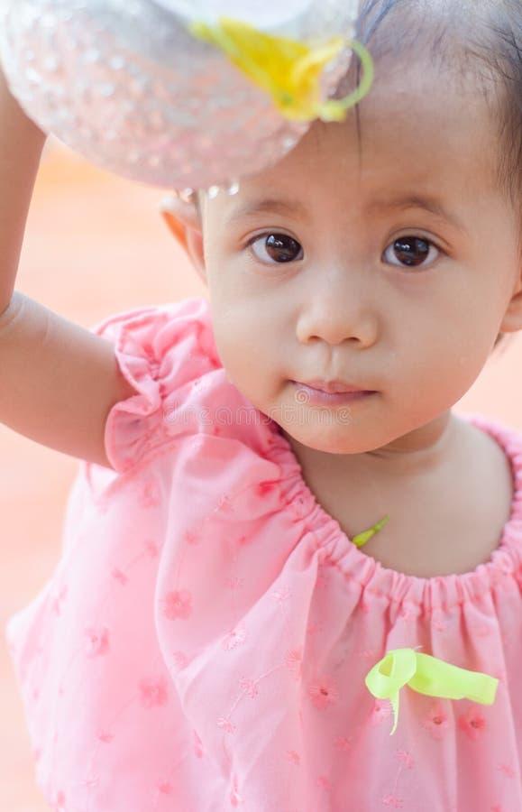 A menina asiática da criança com os trajes tailandeses tradicionais aprecia o splashin fotos de stock royalty free